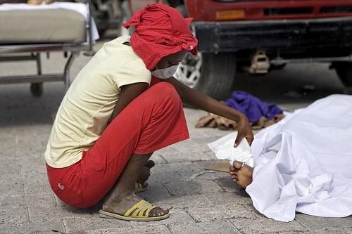 Deceased Quake Victim Laid in Parking Lot of Port-au-Prince Hospital